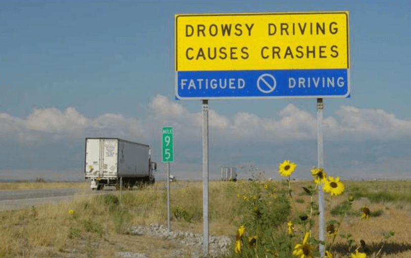 A highway sign says Drowsy Driving causes crashes.